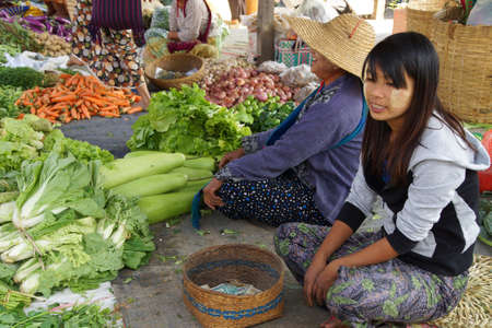 weekly market: INLE LAKE, MYANMAR - MAR 1, 2015 - Young woman selling fresh vegetables at the weekly market on  Inle Lake,  Myanmar (Burma)