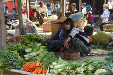 carroty: INLE LAKE, MYANMAR - MAR 1, 2015 - Young woman selling fresh vegetables at the weekly market on  Inle Lake,  Myanmar (Burma)