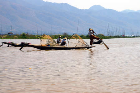 脚ローイング漁師は、インレー湖で, ミャンマー (ビルマ) の彼の小さいボートを推進します。 写真素材 - 48108988
