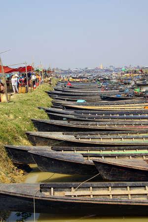 await: INLE LAKE, MYANMAR - MAR 1, 2015 - Empty boats await tourists  at a weekly market on Inle Lake,  Myanmar (Burma) Editorial