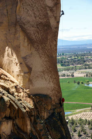 smith rock: Climber dwarfed by the overhanging  cliff of Monkey Face, Smith Rock State Park, Central Oregon