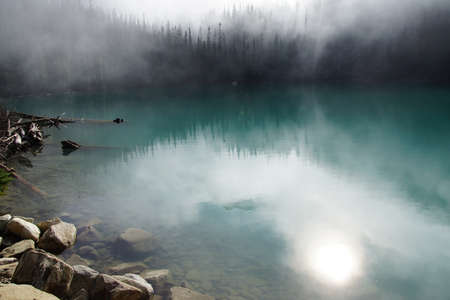 provincial forest parks: Morning mist rising from conifer forest and turquoise lake, Joffre Lakes Provincial Park, British Columbia, Canada