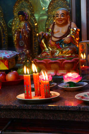 Votive candles and incense, with Buddha statue in the  Emperor Jade Pagoda, Chua Phouc Hai pagoda, Saigon (Ho Chi Minh City),  Vietnam Banco de Imagens - 49470824