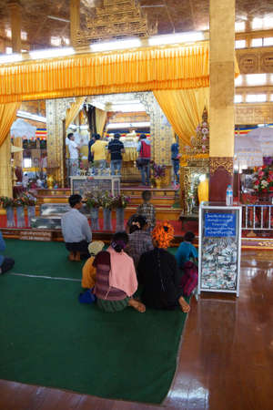 daw: INLE LAKE, MYANMAR - MAR 1, 2015 - Visitors in the huge hall of  Hpaung Daw U Pagoda, Inle Lake,  Myanmar (Burma)