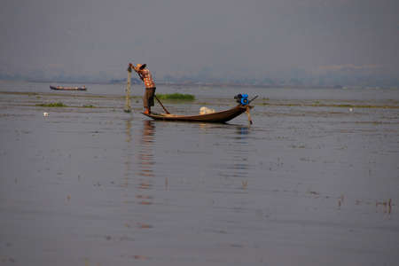 Inle Lake, MYANMAR - 28 februari 2015 - Leg roeien visser zet zijn netten op Inle Lake, Myanmar (Birma)