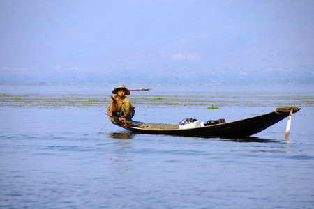 Leg rowing fisherman and his nets in a small boat on Inle Lake,  Myanmar (Burma)