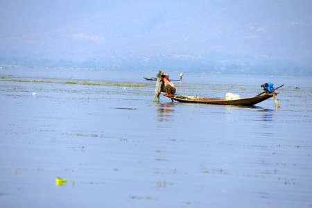 Been roeien visser en zijn netten in een kleine boot op Inle Lake, Myanmar (Birma)