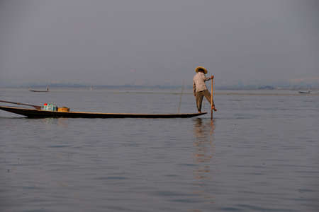 inle: INLE LAKE, MYANMAR - FEB 28, 2015 - Leg rowing fisherman sets his nets on  Inle Lake,  Myanmar (Burma)