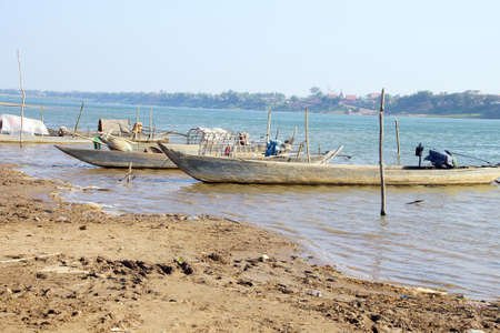 Small boats anchored on the mud flats of the Mekong River near  Kratie, Cambodia