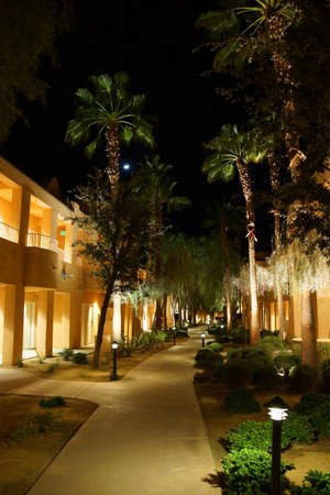 a mirage: RANCHO MIRAGE, CALIFORNIA - DEC 16, 2015 - Night lights of Southwestern style hotel buildings in green oasis with Palm trees,  Rancho Mirage, California