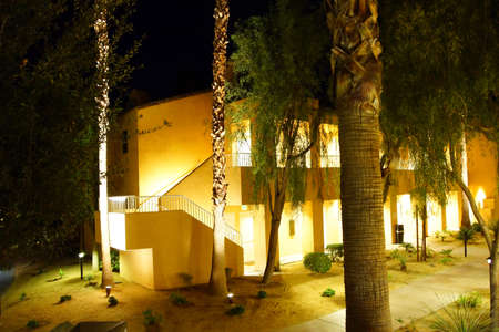 timeshare: RANCHO MIRAGE, CALIFORNIA - DEC 16, 2015 - Night lights of Southwestern style hotel buildings in green oasis with Palm trees,  Rancho Mirage, California