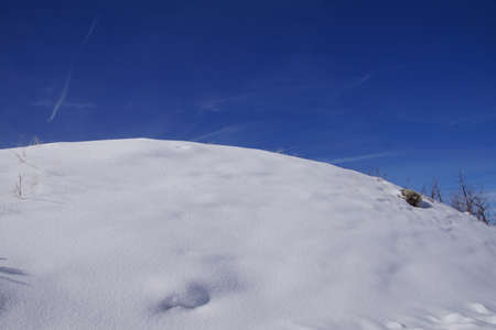 Abstract, snow covered hill and bright blue sky near Cordillera,  Colorado