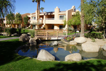 timeshare: RANCHO MIRAGE, CALIFORNIA - DEC 16, 2015 - Southwestern style hotel buildings with ponds in green oasis with Palm trees,  Rancho Mirage, California Stock Photo