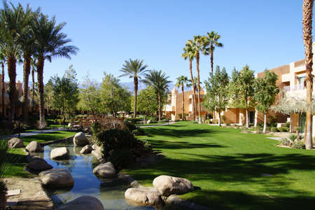 a mirage: RANCHO MIRAGE, CALIFORNIA - DEC 16, 2015 - Southwestern style hotel buildings with ponds in green oasis with Palm trees,  Rancho Mirage, California Editorial