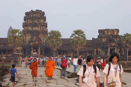 moat wall: ANGKOR WAT, CAMBODIA - FEB 13, 2015 - Sunset, tourists on the causeway across the moat of Angkor Wat,  Cambodia
