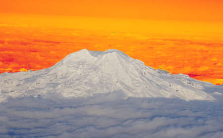 icefall: Mount Rainier with fresh snow and low clouds, aerial view, Washington