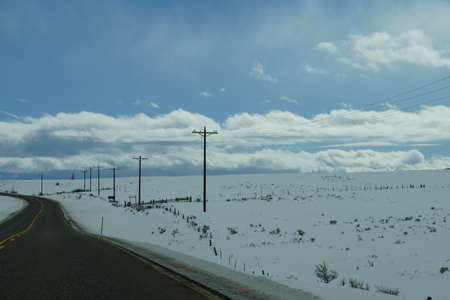 telephone poles: Winter highway with telephone poles and cloudy blue sky, near Yampa,  Colorado