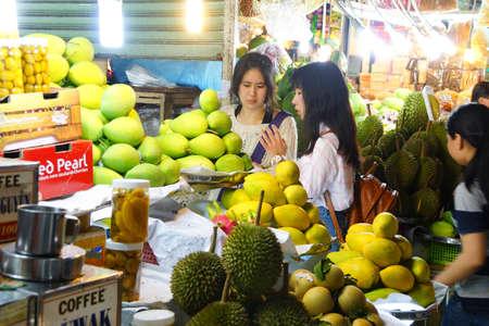 SAIGON - FEB 4, 2015 - Young women buying fruit  at the Ben Thanh market, Saigon (Ho Chi Minh City),  Vietnam