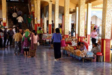 worshipper: INLE LAKE, MYANMAR - MAR 1, 2015 - Visitors in the huge hall of  Hpaung Daw U Pagoda, Inle Lake,  Myanmar (Burma)