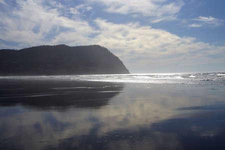 breaks: Afternoon sun dramatically breaks through clouds behind Tilamook Head, with reflections on beach, Seaside, Oregon coast