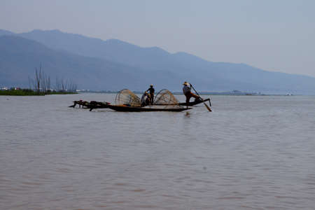 脚ローイング漁師は、インレー湖で, ミャンマー (ビルマ) の彼の小さいボートを推進します。 写真素材 - 51982535