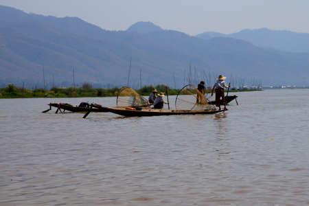 脚ローイング漁師は、インレー湖で, ミャンマー (ビルマ) の彼の小さいボートを推進します。 写真素材 - 52382455