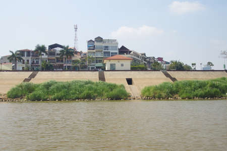 penh: PHNOM PENH, CAMBODIA - FEB 8, 2015 - Buildings along quai of Mekong River , Cambodia