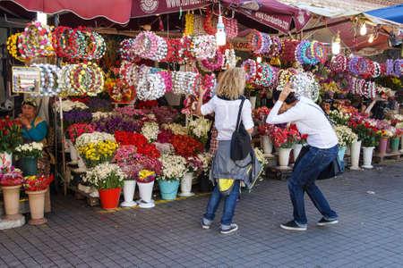 cintillos: ESTAMBUL - 18 DE MAYO, 2014 - Las mujeres jóvenes que tratan de cintas para la cabeza diadema de flores en un jardín de mercado en la plaza de Taksim en Estambul, Turquía Editorial