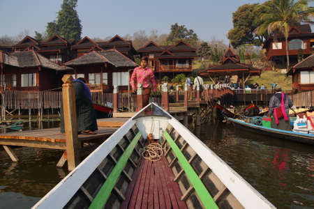 boatman: INLE LAKE, MYANMAR - MAR 1, 2015 - Hotel boatman prepares his boat for a morning tour,  Inle Lake,  Myanmar (Burma) Editorial