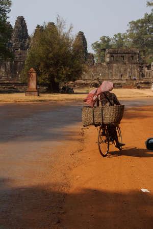 cambodian: Cambodian woman riding bike with large basket near  Angkor Wat,  Cambodia