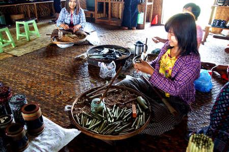 cheroot: INLE LAKE, MYANMAR - MAR 1, 2015 - Young girl rolling cheroot cigars,  Inle Lake,  Myanmar (Burma)