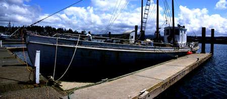 trawler: Old fishing trawler  tied up on a wharf inYaquina Bay, Newport, Oregon Coast Stock Photo