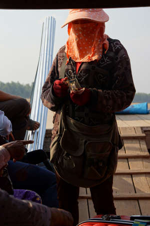 KRATIE, CAMBODIA - FEB 9, 2015 -Woman collects ferry fee from passengers, Kratie Province, Cambodia Editöryel