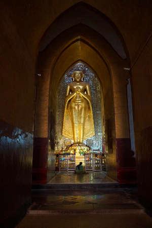 BAGAN, MYANMAR - FEB 25, 2015 - Standing Buddha covered in gold leaf,  Ananda Phaya Temple, Bagan,  Myanmar (Burma)