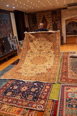 oriental rug: CAPPADOCIA, TURKEY - JUN 4, 2014 - Merchant displays his carpets in  Cappadocia, Turkey