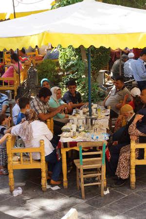 tea house: URFA, TURKEY - JUN 8, 2014 - Extended family relaxes at a tea house  in Urfa bazaar,  Turkey Editorial