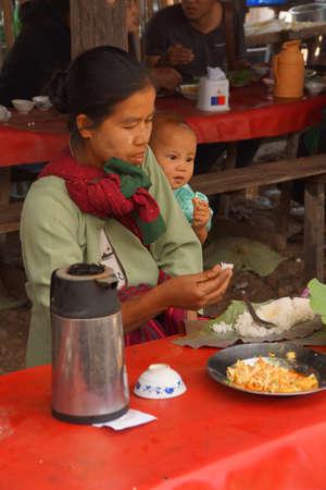 아일 레 호수, 미얀마 - 2015 년 3 월 1 일 - 어머니와 아이가 주간 시장에서 Inle Lake, Myanmar (버마)의 점심을 먹고 있습니다. 에디토리얼