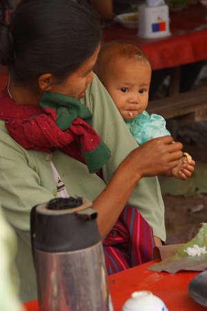 インレー湖で, ミャンマー - 2015 年 3 月 1 日 - 母と子のインレー湖で, ミャンマー (ビルマ) の毎週の市場で昼食を食べて