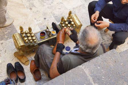 shine: URFA, TURKEY - JUN 8, 2014 - Shoe shine man works  in Urfa bazaar,  Turkey