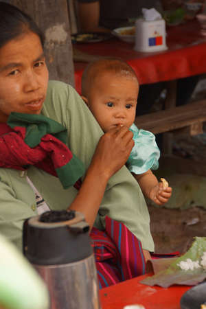 weekly market: INLE LAKE, MYANMAR - MAR 1, 2015 - Mother and child eating lunch at the weekly market on  Inle Lake,  Myanmar (Burma)