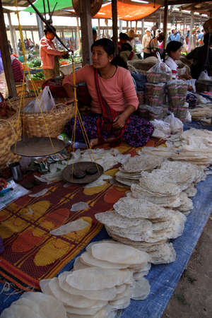 inle: INLE LAKE, MYANMAR - MAR 1, 2015 - Woman selling rice noodles at the weekly market on   Inle Lake,  Myanmar (Burma) Editorial