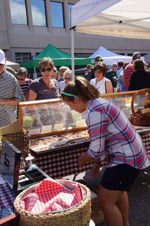 PENTICTON, BRITISH COLUMBIA - JUN 20, 2015 - Woman serving pastries at the  Saturday Market,  Penticton, British Columbia, Canada