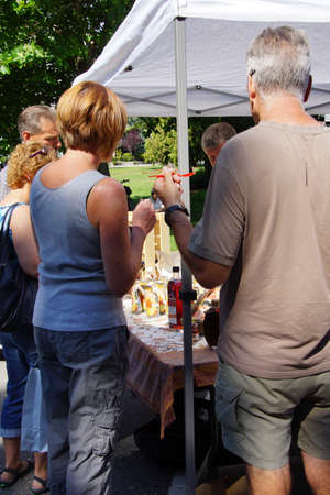 PENTICTON, BRITISH COLUMBIA - JUN 20, 2015 - People tasting syrups and preserves at the  Saturday Market,  Penticton, British Columbia, Canada Editorial
