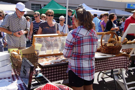 PENTICTON, BRITISH COLUMBIA - JUN 20, 2015 - Woman serving pastries at the  Saturday Market,  Penticton, British Columbia, Canada Stock fotó - 53737395