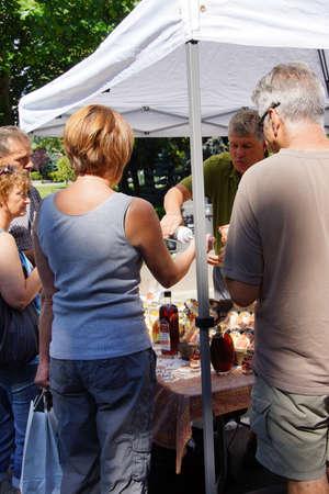 PENTICTON, BRITISH COLUMBIA - JUN 20, 2015 - People tasting syrups and preserves at the  Saturday Market,  Penticton, British Columbia, Canada Stock fotó - 53737506