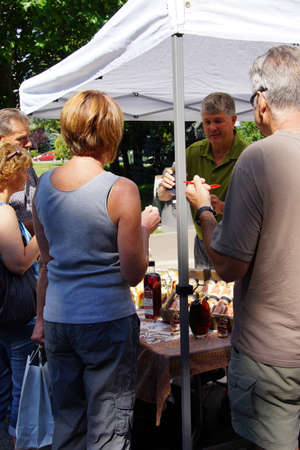british people: PENTICTON, BRITISH COLUMBIA - JUN 20, 2015 - People tasting syrups and preserves at the  Saturday Market,  Penticton, British Columbia, Canada Editorial
