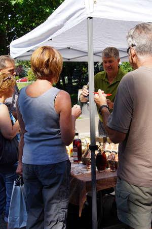 preserves: PENTICTON, BRITISH COLUMBIA - JUN 20, 2015 - People tasting syrups and preserves at the  Saturday Market,  Penticton, British Columbia, Canada Editorial