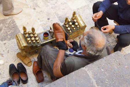 URFA, TURKEY - JUN 8, 2014 - Shoe shine man works in Urfa bazaar, Turkey