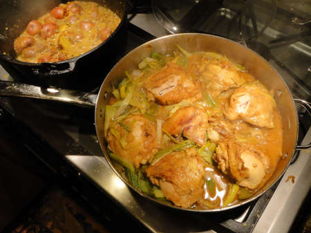 stewing: Coriander chicken curry and curried potatoes cooking in cast iron skillet on gas stove Stock Photo