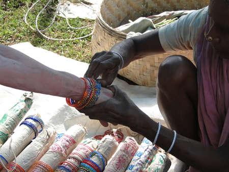 weekly market: Western woman shops for jewelry in weekly market  in Orissa, India